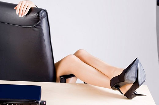 detail of young office worker putting her legs on the desk : Stock Photo
