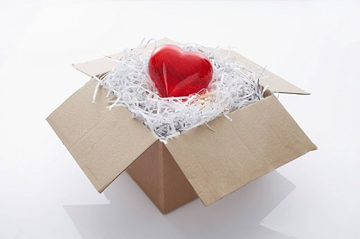 still life of red heart coming out of cardboard box : Stock Photo
