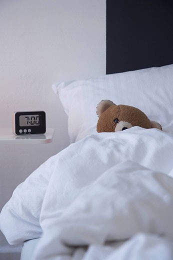still life of teddy bear in bed with alarm clock on sideboard : Stock Photo