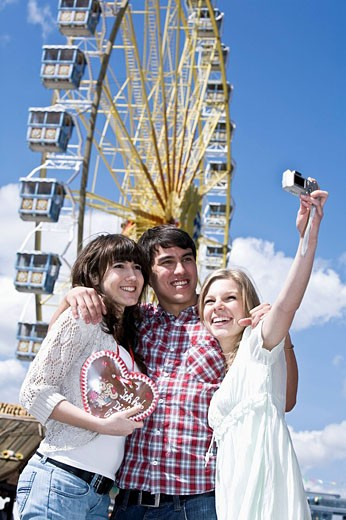 Stock Photo: 1669R-13215 group of three friends at fun fair taking photo of themselves