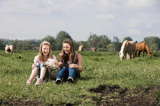 full body portrait of two girls sitting on meadow with dog at horse ranch : Stock Photo