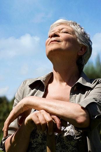 portrait of mature woman in garden enjoying the summer sun : Stock Photo