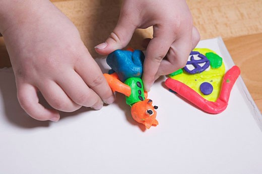 close_up of young girl playing with modelling clay : Stock Photo