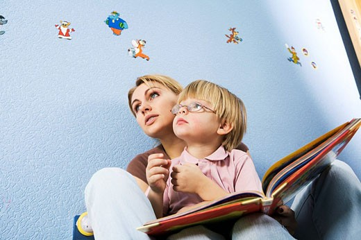 young mother and son reading book together : Stock Photo