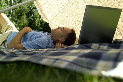 Stock Photo: 1669R-1417 man with his laptop computer under a sunshade, dozing