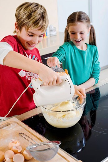 Stock Photo: 1669R-14172 brother and sister mixing dough in bowl together