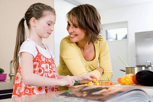 mother watching her daughter cutting vegetables : Stock Photo