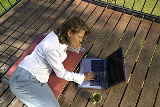 woman lying on porch working with laptop computer : Stock Photo