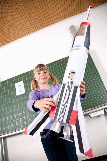 Stock Photo: 1669R-15822 portrait of young girl in classroom holding model of rocket