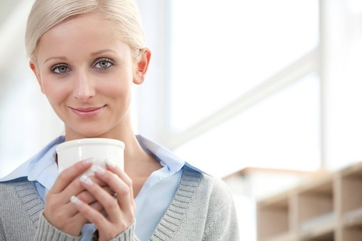 portrait of young blonde woman holding cup : Stock Photo
