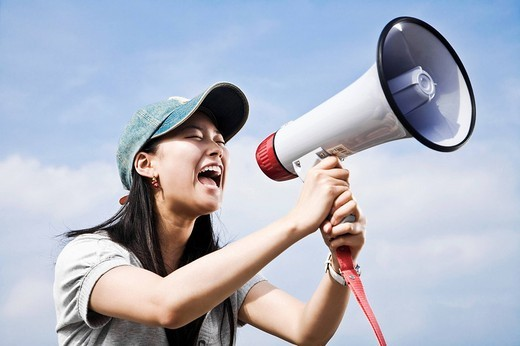 Stock Photo: 1669R-17327 portrait of young japanese woman shouting through megaphone
