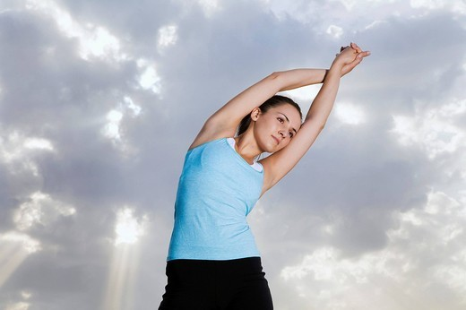 Stock Photo: 1669R-17361 portrait of young jogger doing stretching exercises in park