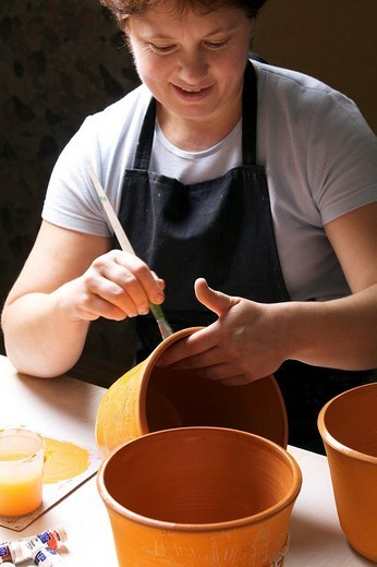woman painting jar in workshop : Stock Photo