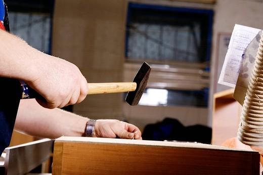 Stock Photo: 1669R-18025 detail of craftsman assembling furniture using hammer and nail