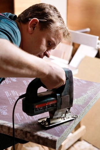 craftsman cutting wood with jigsaw : Stock Photo