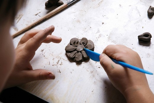 young girl forming flower out of clay : Stock Photo