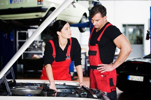 female and male mechanic having discussion in garage : Stock Photo