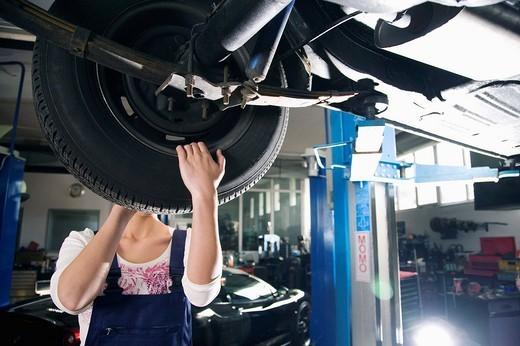 female mechanic changing tire on car : Stock Photo