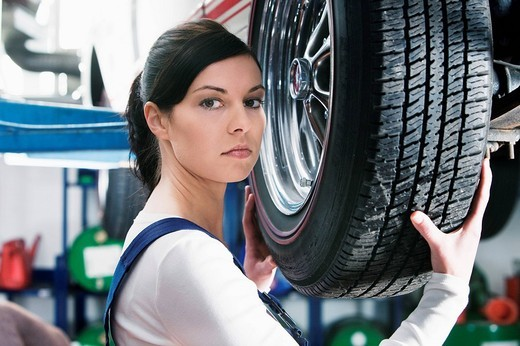 headshot of female mechanic changing tire on car : Stock Photo