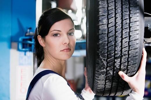 headshot of female mechanic changing tire on car : Stock Photo