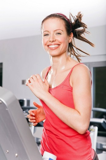 Stock Photo: 1669R-18202 young woman exercising on treadmill in gym