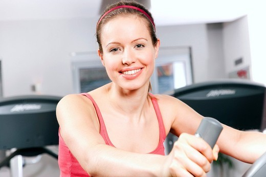 Stock Photo: 1669R-18207 young woman exercising with stationary bicyle in gym