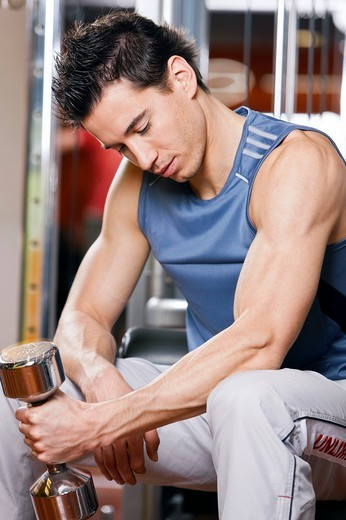 Stock Photo: 1669R-18260 young man exercising with dumb bell