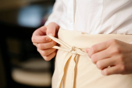 close_up of waitress in restaurant tying apron : Stock Photo