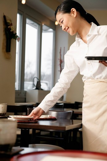 portrait of young japanese waitress setting table at restaurant : Stock Photo