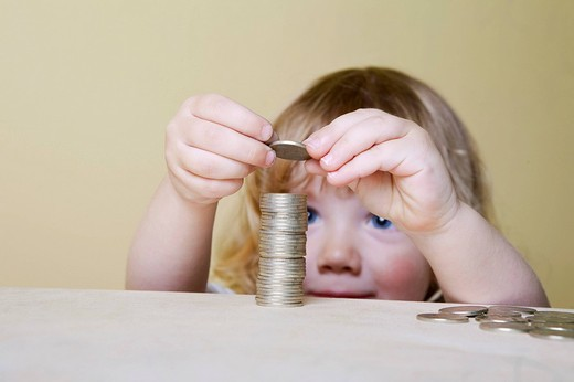 young boy making pile of coins : Stock Photo