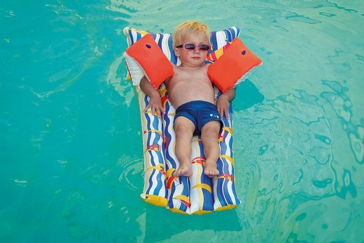 young boy lying on air bed floating in swimming pool : Stock Photo