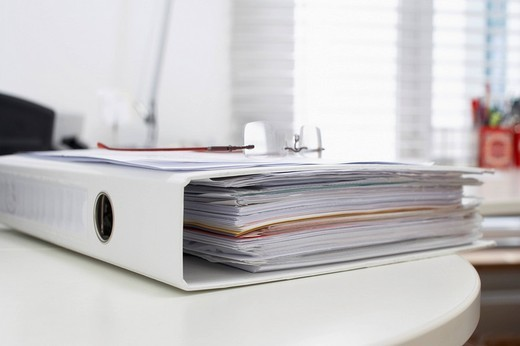 file and glasses lying on table : Stock Photo