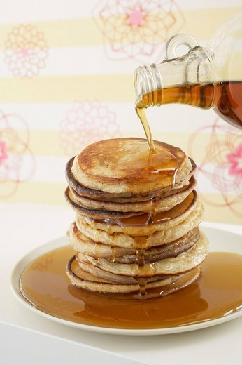 Stock Photo: 1669R-19249 maple syrup being poured over pancakes