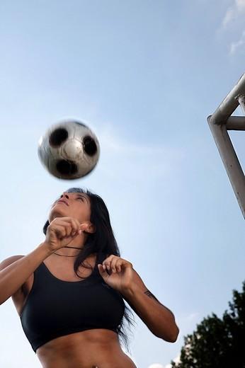 female football player practising header : Stock Photo