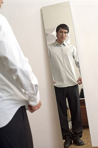 Teenage boy checking his appearance in the mirror : Stock Photo