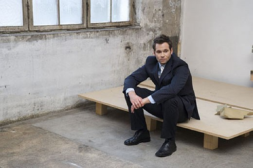 Stock Photo: 1669R-2829 disappointed looking businessman sitting in empty factory building