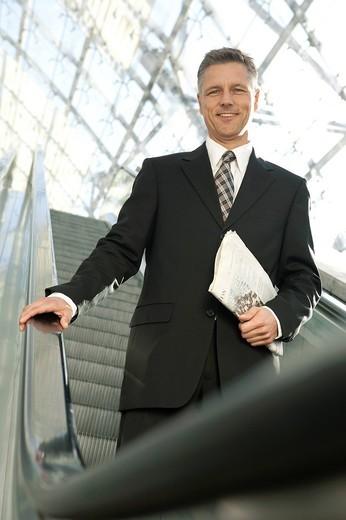 businessman standing on escalator : Stock Photo