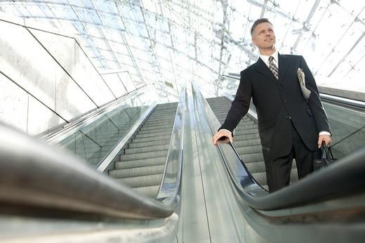 Stock Photo: 1669R-31344 businessman standing on escalator
