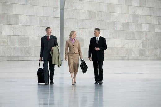 three business people walking through hall : Stock Photo