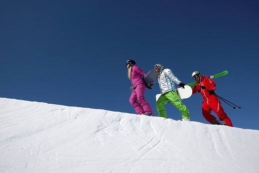 group of three people with skis and snowboards walking up mountain : Stock Photo