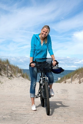 portrait of young woman on bicycle at beach : Stock Photo