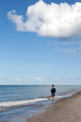 Stock Photo: 1669R-31599 young boy standing on beach