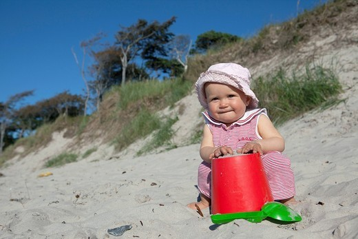 Stock Photo: 1669R-31609 portrait of baby girl playing in sand on beach