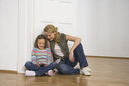 mother watching her little girl playing with gameboy : Stock Photo