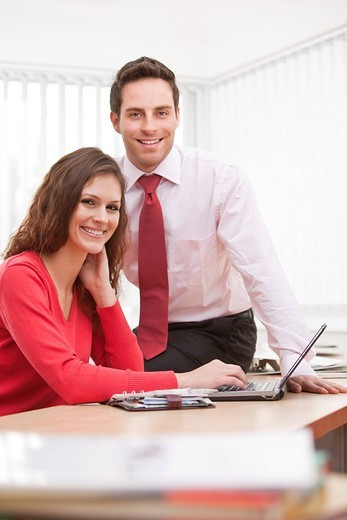 Stock Photo: 1669R-31785 portrait of young businesswoman and male colleague sitting at desk