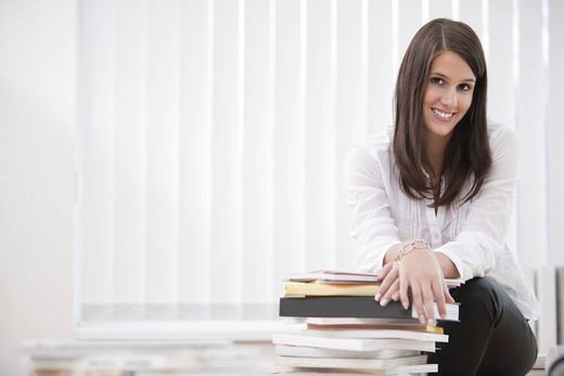 Stock Photo: 1669R-31862 portrait of young businesswoman sitting on desk