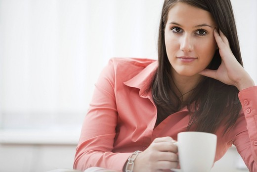 Stock Photo: 1669R-31869 portrait of young businesswoman sitting at desk with cup