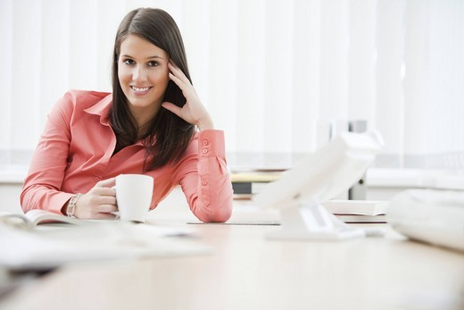 Stock Photo: 1669R-31870 portrait of young businesswoman sitting at desk with cup