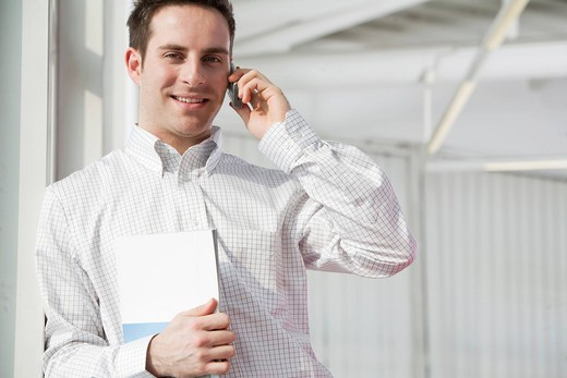 Stock Photo: 1669R-31890 portrait of young businessman talking on mobile phone
