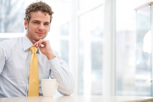 portrait of young businessman sitting at desk with cup : Stock Photo